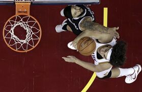 Cleveland Cavaliers' Anderson Varejao, bottom, from Brazil, drives to the basket against Brooklyn Nets' Deron Williams, top, during the first half of an NBA basketball game Friday, Dec. 19, 2014, in Cleveland. (AP Photo/Tony Dejak)