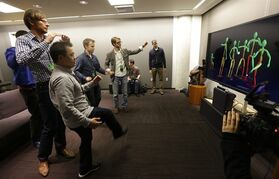 A group of visiting journalists try out the improved motion-detecting capabilities of the new Kinect controller for Microsoft's next-generation Xbox One entertainment and gaming console system, Tuesday, May 21, 2013, in Redmond, Wash. The new Kinect, which will come standard with the Xbox One can also see users in total darkness and has a wider field of view than the previous Kinect device in use with the Xbox 360. (AP Photo/Ted S. Warren)