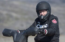 Canadian Prime Minister Stephen Harper drives an all terrain vehicle across the tundra Tuesday August 26, 2014 on Baffin Island near York Sound, Nunavut. THE CANADIAN PRESS/Adrian Wyld