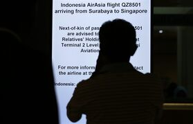 A man is silhouetted against an electronic sign board instructing relatives and next-of-kin to gather at a holding area at the Changi International Airport where AirAsia Flight 8501 from Surabaya, Indonesia was scheduled to land, Sunday, Dec. 28, 2014 in Singapore. The AirAsia plane disappeared Sunday while flying over the Java Sea after taking off from Indonesia's second-largest city for Singapore. (AP Photo/Wong Maye-E)