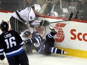 Winnipeg Jets Bryan Little (18) goes down in a cloud of ice against Los Angeles Kings defenceman Drew Dougherty in first period action at the MTS Center Thursday, March 6.