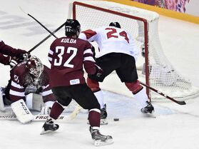 Canada forward Corey Perry and Latvia goalie Kristers Gudlevskis scramble to find a loose puck as Latvia defenceman Arturs Kulda looks on during first period quarter-final hockey action at the 2014 Winter Olympics in Sochi, Russia on Wednesday. With their 2-1 win Canada now advances to the gold medal game against USA Friday morning at 11 a.m