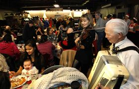 Isaiah, 5 months old, sits on his mother Allyson Kerr's lap and enjoys the Christmas carols performed by Daria Watkin and Bjarnie