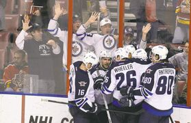 It was worth the trip: Winnipeg Jets fans celebrate their team's overtime win against the Florida Panthers on Friday night. A Panthers fan tries to ignore the interlopers.