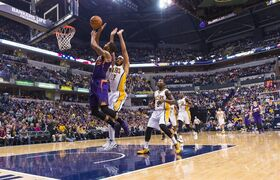 Phoenix Sun's Marcus Morris (15) takes the ball to the basket off a fast-break against Indiana Pacer's Chris Copeland (22) during the first half of an NBA basketball game, Saturday, Nov. 22, 2014, in Indianapolis. (AP Photo/Doug McSchooler)