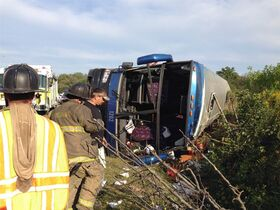 FILE - In this Sept. 21, 2014 file photo, passengers from a tour bus are treated for injuries near the overturned bus at the Tybouts Corner onramp from southbound Delaware 1 to Red Lion Road in Bear, Del. Recordings obtained by The Associated Press under the Freedom of Information Act indicate that 911 operators struggled to learn exactly where the crash occurred because passengers didn't know where they were. (AP Photo/The Wilmington News-Journal, John J. Jankowski, File)