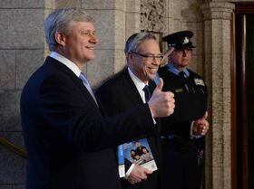 Prime Minister Stephen Harper accompanies Finance Minister Joe Oliver as he makes his way to deliver the federal budget in the House of Commons on Parliament Hill in Ottawa on Tuesday, April 21, 2015.
