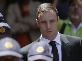 FILE - In this Friday, Oct. 17, 2014 file photo, Oscar Pistorius is escorted by police officers as he leaves the high court in Pretoria, South Africa. A spokesman for South Africa's National Prosecuting Authority said Monday, Oct. 27, 2014 that prosecutors will appeal the verdict and sentencing of Oscar Pistorius, who was handed a 5-year prison term after being convicted of culpable homicide. (AP Photo/Themba Hadebe, File)