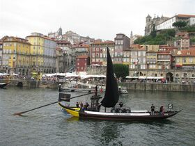 This June 2014 photo shows a rabelos boat, which were used to transport port wine from the vineyards down to Gaia, on the Douro river in front of Porto's historic Ribeira district in Portugal. These mountain-hugging terraced vineyards produce one of the most recognizable wines in the world and the most visible export of this economically struggling country. (AP Photo/Giovanna Dell'Orto)