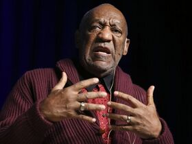FILE - In this Nov. 6, 2013 file photo, Comedian Bill Cosby performs at the Stand Up for Heroes event at Madison Square Garden in New York. Biographer Mark Whitaker, whose