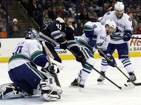 Columbus Blue Jackets' Scott Hartnell (43) works for the puck between Vancouver Canucks goalie Ryan Miller (30), Ryan Stanton (18), and Luca Sbisa (5), of Italy, during the second period of an NHL hockey game in Columbus, Ohio, Friday, Nov. 28, 2014. (AP Photo/Paul Vernon)
