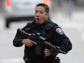 An Ottawa police officer runs with his weapon drawn in Ottawa on Wednesday after a gunman opened fire  and killed a soldier at the National War Memorial near Parliament Hill.