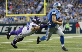 Detroit Lions quarterback Matthew Stafford (9) outruns Minnesota Vikings defensive end Brian Robison (96) during the first half of an NFL football game at Ford Field in Detroit, Sunday, Dec. 14, 2014. (AP Photo/Rick Osentoski)