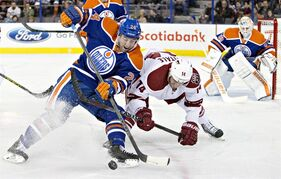 Arizona Coyotes' Joe Vitale (14) and Edmonton Oilers' Brad Hunt (24) battle for the puck as goalie Ben Scrivens (30) looks on during first period NHL hockey action in Edmonton, Alta., on Tuesday December 23, 2014. THE CANADIAN PRESS/Jason Franson