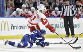 Detroit Red Wings right wing Luke Glendening (41) takes down Tampa Bay Lightning center Alex Killorn (17) as they chase a loose puck during the first period of an NHL hockey game Thursday, Jan. 29, 2015, in Tampa, Fla. (AP Photo/Chris O'Meara)