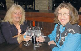 Food Musings columnist Kathryne Grisim (left) and contest winner Janice Sawka clink glasses in anticipation of the meal Kathryne will treat Janice to at The Keg.