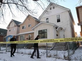 Detectives arrive at a crime scene at a rooming house at 500 Victor Street Friday afternoon.