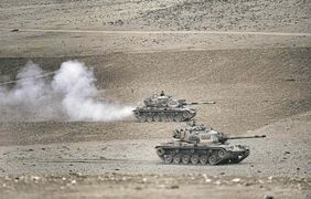Burhan Ozbilici / The Associated PressTurkish tanks roll to take positions along the Turkey-Syria border Monday.