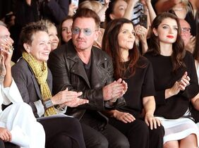 FILE- In this Sept. 7, 2014 file photo released by Starpix, Laurie Anderson, from left, Bono, Ali Hewson, and Eve Hewson sit in the front row during the Edun Spring 2015 collection during Fashion Week in New York. Bono says his ever-present sunglasses aren't a rock-star affectation — he has suffered from glaucoma for 20 years. told the BBC's