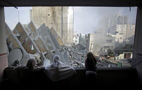 FILE - In this Tuesday, Aug. 26, 2014 file photo, a Palestinian family looks from a window at the rubble of the collapsed 15-story Basha Tower following early morning Israeli airstrikes in Gaza City. The Palestinian economy is expected to contract for the first time in seven years in 2014, the result of the recent Gaza war, continued Israeli and Egyptian restrictions on Palestinian trade and a drop in foreign aid, the World Bank said Tuesday. (AP Photo/Khalil Hamra, File)