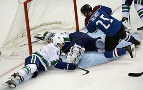 Colorado Avalanche center Maxime Talbot, right, has his shot stopped by Vancouver Canucks goalie Eddie Lack, center, of Sweden, as Canucks' defenseman Christopher Tanev covers in the first period of an NHL hockey game in Denver, Friday, Oct. 24, 2014. (AP Photo/David Zalubowski)