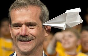 Retired Canadian astronaut Chris Hadfield gets hit in the head by a paper airplane as he takes part in a paper airplane toss with some 60 grade five students in Coquitlam, B.C. Thursday, April 17, 2014. THE CANADIAN PRESS/Jonathan Hayward