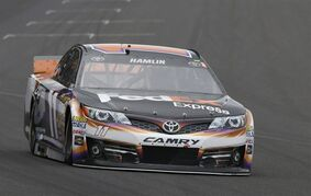 Denny Hamlin drives into Turn 1 during the NASCAR Brickyard 400 auto race at Indianapolis Motor Speedway in Indianapolis, Sunday, July 27, 2014. (AP Photo/Tom Strattman)