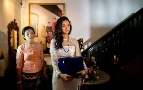 May Myat Noe, right Myanmar's first international beauty queen, winner of the 2014 Miss Asia Pacific World, walks with her mother San San Htwe for a press conference while carrying her crown that she allegedly ran away with, in Yangon, Myanmar Tuesday, Sept. 2, 2014. The dethroned beauty queen from Myanmar said she won't return her $100,000 worth crown until the pageant's organizers apologize for calling her a liar and a thief. (AP Photo/Gemunu Amarasinghe)