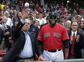FILE - In this Oct. 4, 2013 file photo, Boston Mayor Tom Menino, left, throws out the ceremonial first pitch beside Boston Red Sox designated hitter David Ortiz, center, and Red Sox owner John Henry, right, before Game 1 of baseball's American League division series between the Sox and the Tampa Bay Rays in Boston. Menino, who was diagnosed with cancer a month after leaving office at the end of 2013, died Thursday, Oct. 30, 2014 in Boston. He was 71. (AP Photo/Charles Krupa, File)