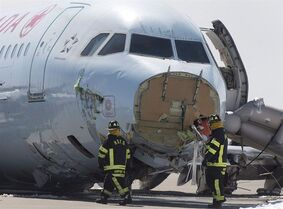 Airport firefighters work at the crash site of Air Canada AC624 that crashed early Sunday morning during a snowstorm, at Stanfield International Airport in Halifax on Monday, March 30, 2015. A law firm says it has filed a $12-million class action lawsuit on behalf of passengers involved in a plane crash at Halifax's airport last month. THE CANADIAN PRESS/Andrew Vaughan