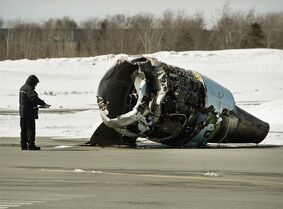 A Transportation Safety Board invesigator inspects an engine at the crash site of Air Canada AC624 that crashed early Sunday morning during a snowstorm, at Stanfield International Airport in Halifax on Monday, March 30, 2015. The flight had 133 passengers and five crew members. THE CANADIAN PRESS/Andrew Vaughan-Pool