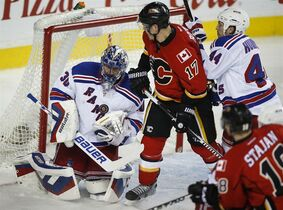 New York Rangers goalie Henrik Lundqvist, left, from Sweden, juggles the puck as Calgary Flames' Lance Bouma looks on during third period NHL hockey action in Calgary, Tuesday, Dec. 16, 2014.THE CANADIAN PRESS/Jeff McIntosh