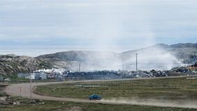 A car approaches a smouldering fire burning at the city dump in Iqaluit, Nunavut, Thursday July 10, 2014. The military fretted over fumes coming off Iqaluit's notorious dump fire during this summer's Arctic training exercise, new documents show. THE CANADIAN PRESS/Adrian Wyld