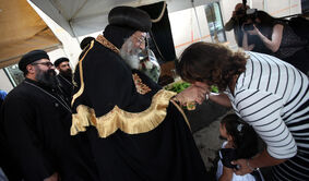 A Coptic Orthodox worshipper kisses the hand of Pope Tawadros II during the spiritual leader's visit to Winnipeg on Sept. 19.