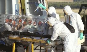 FILE - In this Aug. 7, 2014 file photo provided by the Spanish Defense Ministry, aid workers and doctors transfer Miguel Pajares, a Spanish priest who was infected with the Ebola virus while working in Liberia, from a plane to an ambulance as he leaves the Torrejon de Ardoz military airbase, near Madrid, Spain. Comparisons between Ebola and AIDS have surfaced in mid-2014 as the Ebola outbreak escalated. But Ebola is not expected to ever be in the same league as AIDS in terms of infections and deaths, said Dr. Anthony Fauci, director of the National Institute of Allergy and Infectious Diseases. (AP Photo/Spanish Defense Ministry, File)