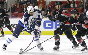 Carolina Hurricanes' Jay Harrison (44) and Jay McClement (18) defend Winnipeg Jets' Dustin Byfuglien (33) during the first period of an NHL hockey game in Raleigh, N.C., Thursday.