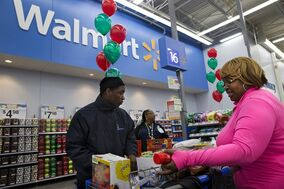 FILE - In this Dec. 4, 2013 file photo, April Taylor of Upper Marlboro, Md., right, buys items with her son Jarhon Taylor, left, on the opening day of a new Wal-Mart in Washington. Wal-Mart Stores Inc. on Thursday, Oct. 30, 2014 said it is considering matching online prices from competitors like Amazon.com, raising the stakes for the holiday shopping season. (AP Photo/Jacquelyn Martin, File)
