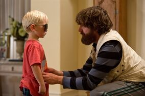 This film publicity image released by Warner Bros. Pictures shows Grant Holmquist as Tyler/Carlos, left, and Zach Galifianakis as Alan in a scene from