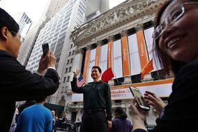 Arthur Jiang, of Beijing, China, poses for a photograph in front of the New York Stock Exchange on the day of Alibaba's initial public offering, Friday, Sept. 19, 2014 in New York. The Chinese e-commerce giant goes public Friday in a record busting share sale. (AP Photo/Jason DeCrow)
