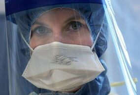 Nurse Lori Fleetwood shows off the personal protective equipment health care workers would wear when treating patients with suspected cases of Ebola.