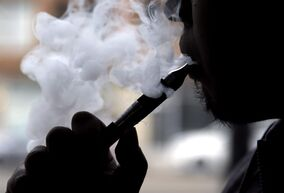 A man demonstrates an e-cigarette at a store in Chicago, in an April 23, 2014 file photo, B.C.'s health minister is regulating electronic cigarettes with new legislation that will ban sales to young people and prohibit their use in indoor public spaces and workplaces. THE CANADIAN PRESS/AP/Nam Y. Huh