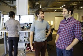 In this photo taken Thursday, April 3, 2014, Asana co-founders Justin Rosenstein, center, and Dustin Moskovitz, right, pose for photos at the company's headquarters in San Francisco. Asana peddles software that combines the elements of a communal notebook, social network, instant messaging application and online calendar to enable teams of employees to share information and do most of their jobs without relying on email. (AP Photo/Eric Risberg)