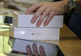 FILE - In this Sept. 19, 2014 file photo, an Apple store employee checks out a customer who bought two iPhone 6 smartphones, in New York. Apple on Monday, Oct. 20, 2014 said it sold 39.3 million iPhones in the last quarter, or 16 percent more than a year ago, which is a record for the quarter. That's partly due to excitement over new iPhone 6 and 6 Plus models that Apple began selling last month. (AP Photo/Julie Jacobson, File)