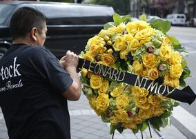 """A florist sets memorial flowers on the Hollywood Walk of Fame star of actor Leonard Nimoy in Los Angeles, Friday, Feb. 27, 2015. Nimoy, famous for playing officer Mr. Spock in """"Star Trek"""" died Friday, Feb. 27, 2015, in Los Angeles of end-stage chronic obstructive pulmonary disease. He was 83. (AP Photo/Damian Dovarganes)"""