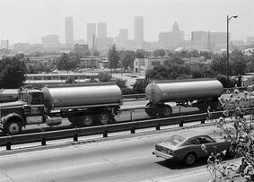 FILE - This June 28, 1979 file photo shows a double-trailer flammable truck driving along the Santa Ana Freeway with a skyline of Los Angeles as a backdrop from East Los Angeles. A study appearing in the Thursday, March 5, 2015, issue of the New England Journal of Medicine that children in recent years breathed cleaner air and had stronger lungs compared to those who were studied two decades earlier, researchers found. (AP Photo/Wally Fong, File)