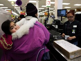 An Innu child is carried in an amautik by her mother who is paying for groceries in Baker Lake, Nunavut on March 25, 2009. THE CANADIAN PRESS/Nathan Denette