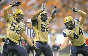 The Blue's Louie Richardson (from left), Bryant Turner Jr. and Zach Anderson celebrate a sack Friday.