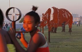 In this photo taken on Sunday, Aug. 24, 2014, a child stands next to an artistic piece on the promenade showing the crosshairs, left, of a rifle scope, with a Rhino body in the background in Cape Town, South Africa. It forms part of a public art display to emphasize the number of Rhinos being killed in South Africa by rhino poachers for the use of its horn in eastern medicine. The promenade offers a temporary art project, art54, with new pieces exhibited from time to time. (AP Photo/Schalk van Zuydam)