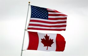 Canadian and American flags fly in Point Roberts, Wash., on Tuesday March 13, 2012. Canada, the next-door neighbour known for its socialized medicine, liberal social policy, and aversion to the Iraq war is now perceived through a slightly different prism: big oil, small corporate taxes, and hawkish rhetoric against Putin and ISIL.THE CANADIAN PRESS/Darryl Dyck
