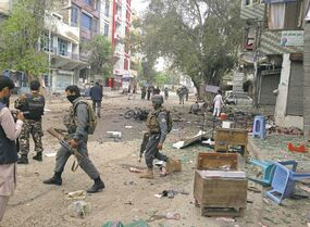 The Associated PressAfghan security forces members inspect the site of a suicide attack near a bank in Jalalabad Saturday.